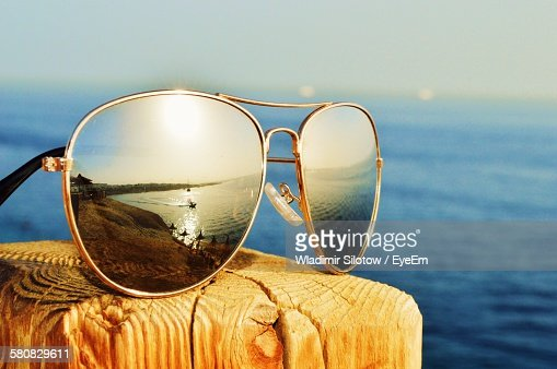 Close-Up Of Reflection In Sunglasses On Wood Against Sea