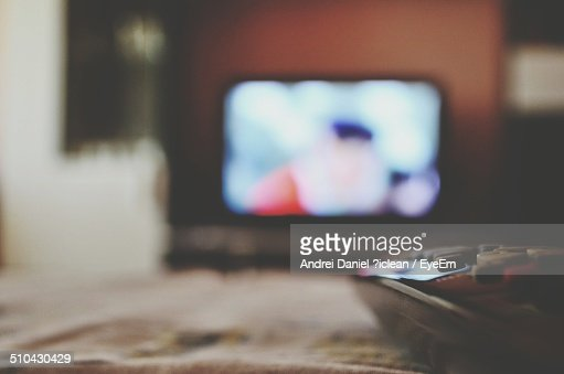 Close-up of remote control with blurred television in distance