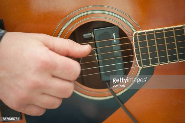 Closeup of right hand of guitar player strumming on an amplified folk guitar in Easton MD