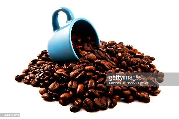 Close-Up Of Roasted Coffee Beans With Cup Against White Background