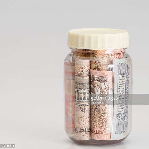 Close-up of rolled up bundles of Indian banknotes of different denominations in a jar