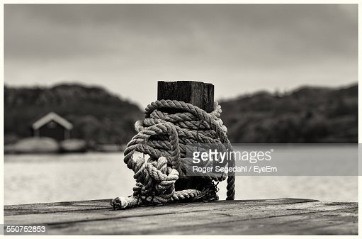 Close-Up Of Rope Tied To Bollard On Pier By Lake Against Sky