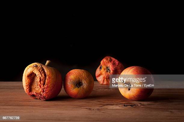 Close-Up Of Rotten Apples On Table Against Black Background