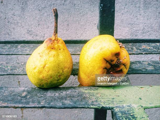 Close-Up Of Rotting Pears On Metal Bench Against Wall