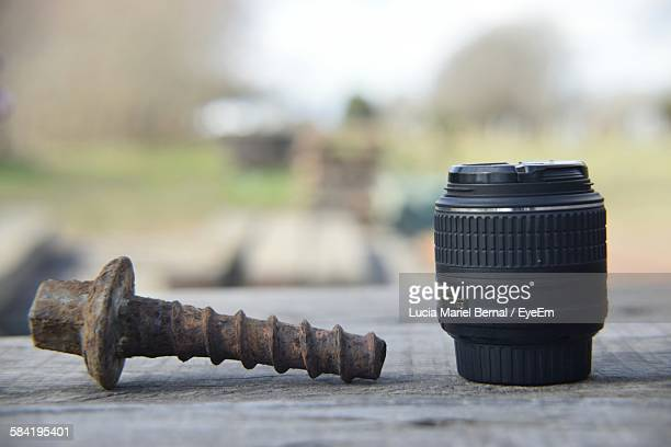 Close-Up Of Rusty Nut With Camera Lens On Wooden Texture