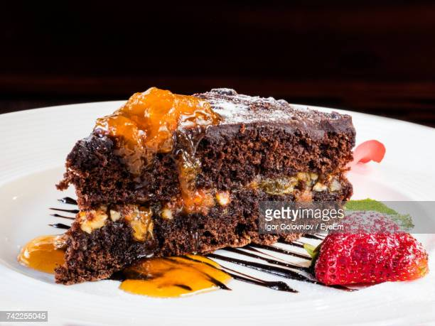 Close-Up Of Sacher Cake Served With Strawberry In Plate On Red Table