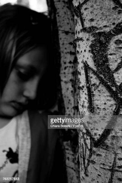 Close-Up Of Sad Girl Leaning On Tree