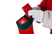 Close-up of santa claus putting presents in christmas stockings against white background