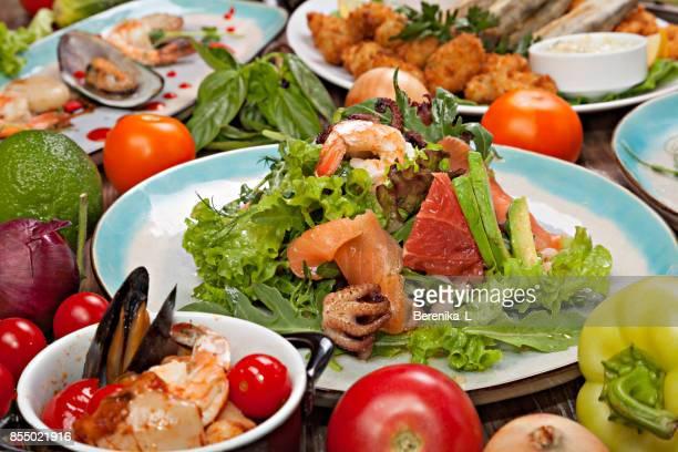 Gros plan de salade de fruits de mer sur le fond de légumes, les herbes et les divers plats de la carte du restaurant.