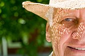 Close-up of senior man smiling in hat