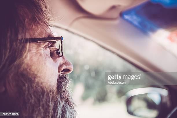 Close-up of Senior Man with Glasses and Beard Driving