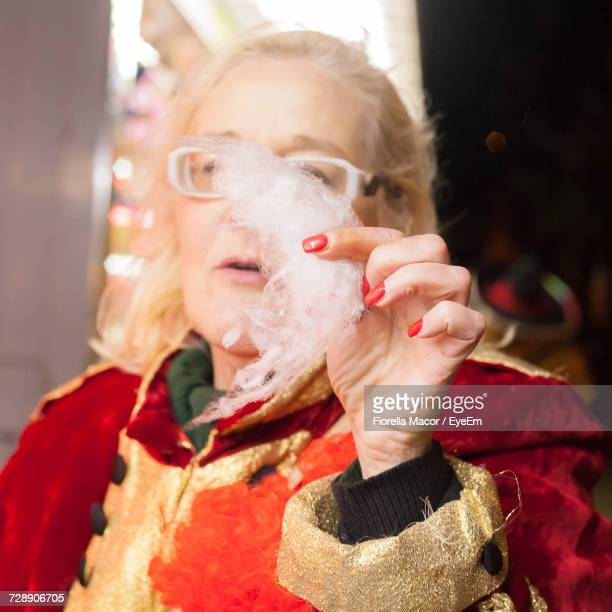 Close-Up Of Senior Woman In Carnival Holding Cotton Candy