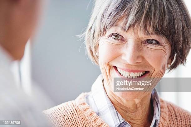 Close-up of senior woman in conversation smiling widely