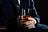 Closeup of serious businessman holding glass of whisky illustrate executive privilege concept.