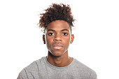 Close-up portrait of serious looking teenager. African teenage boy looking at camera against white background.