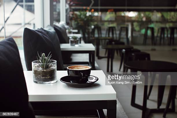 Close-Up Of Served Coffee Cup With Potted Plant