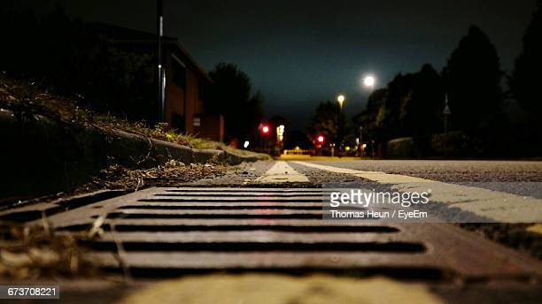 Close-Up Of Sewer On Road At Night