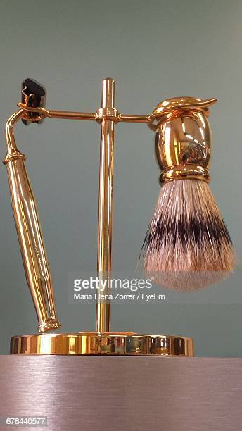 Close-Up Of Shaving Brush And Razor On Stand Against Wall
