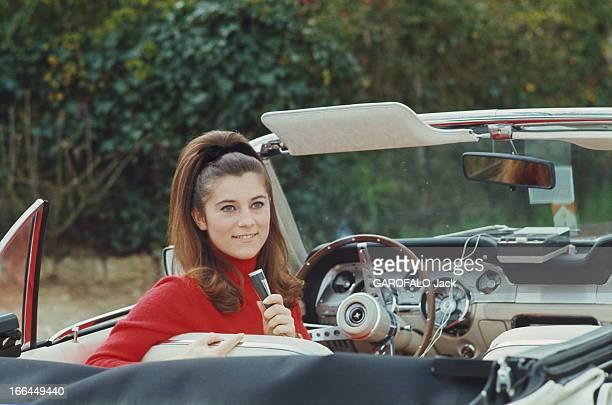 CloseUp Of Sheila Attitude souriante de SHEILA assise au volant d'une Ford Mustang cabriolet un petit micro à la main