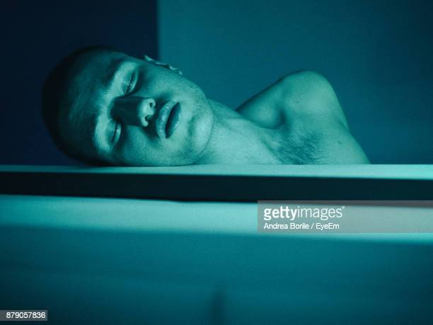 Close-Up Of Shirtless Young Man Sleeping In Bathtub At Home