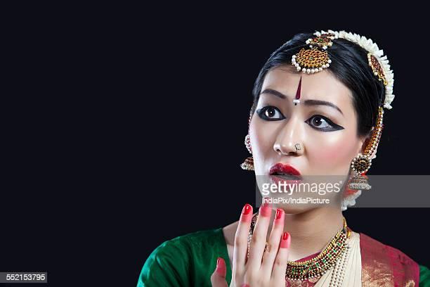 Close-up of shocked Bharatanatyam dancer performing on black background