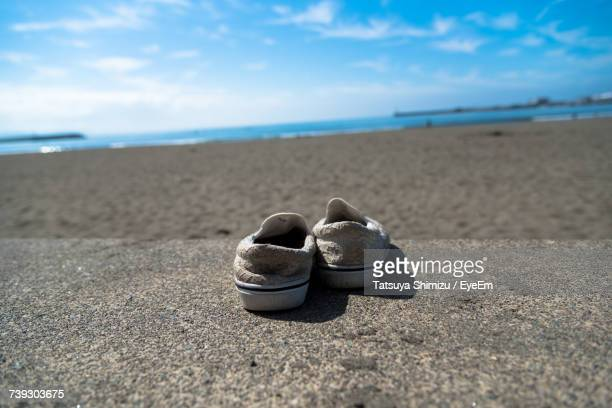 Close-Up Of Shoes On Sand At Beach Against Sky