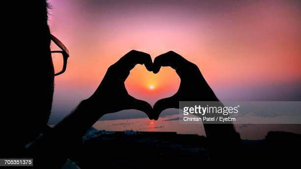 Close-Up Of Silhouette Hand Holding Heart Shape Against Sky During Sunset