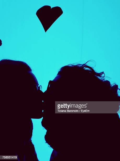 Close-Up Of Silhouette Lesbian Couple Kissing By Illuminated Turquoise Light