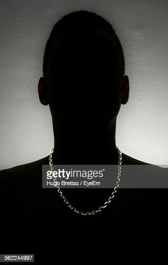 Close-Up Of Silhouette Man With Gold Chain Against White Wall