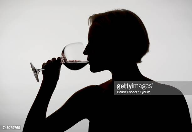Close-Up Of Silhouette Woman Drinking Red Wine Against White Background
