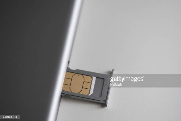 Close-up of sim card and mobile phone on white table