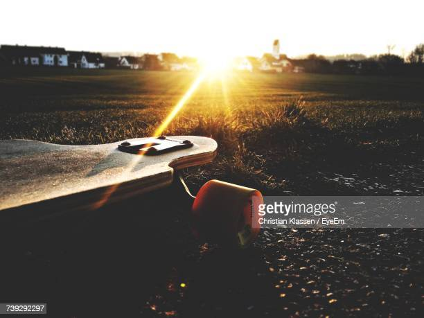 Close-Up Of Skateboard On Field Against Sky During Sunset