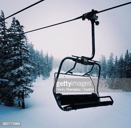 Close-Up Of Ski Lift Above Snowcapped Mountains During Winter