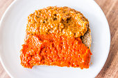 Closeup of slice piece of whole wheat sprouted toasted grain bread on plate with orange red bell pepper vegetable eggplant spread on table macro flat top down view