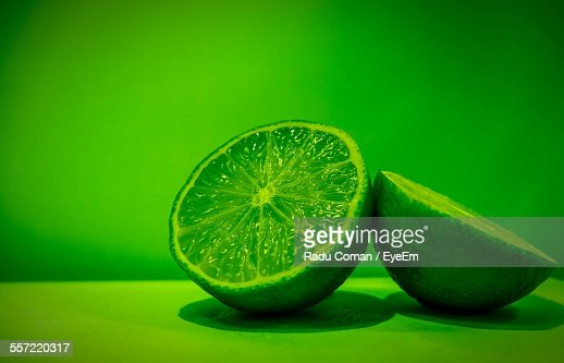 Close-Up Of Sliced Lime On Table Against Green Background