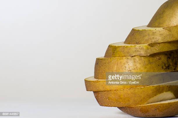 Close-Up Of Sliced Pear Against White Background