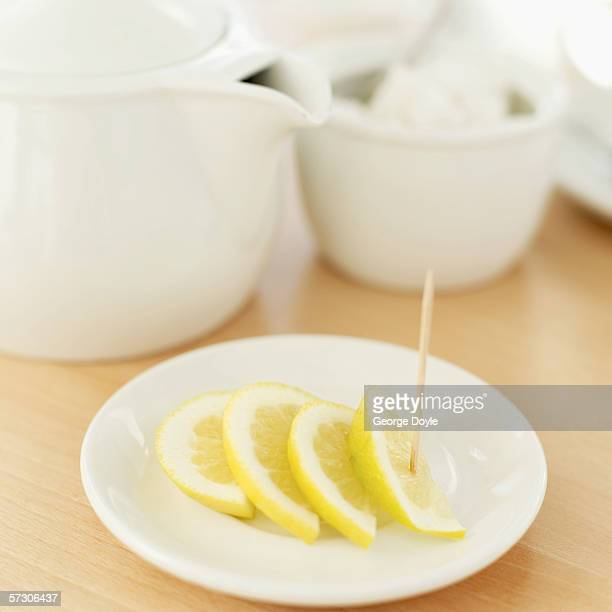 Close-up of slices of lemon on a plate with a toothpick and teapot and teabags in a bowl