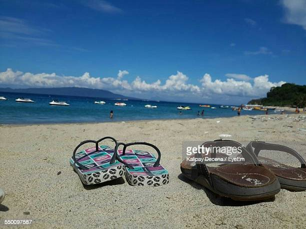 Close-Up Of Slippers On Beach Against Blue Sky