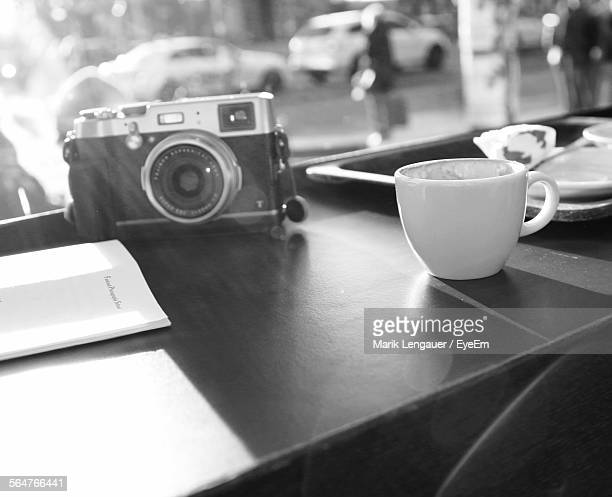 Close-Up Of Slr Camera With Tea Cup