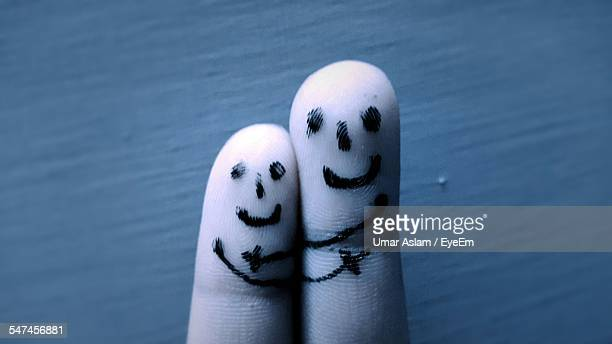 Close-Up Of Smiles Drawn On Finger Against Wall