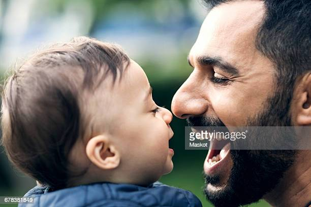 Close-up of smiling father and toddler at park