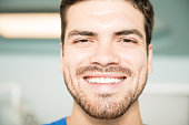 Closeup portrait of smiling mid adult male patient at dental clinic