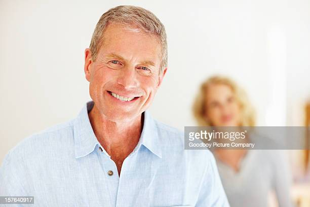 Close-up of smiling senior man with woman in the background
