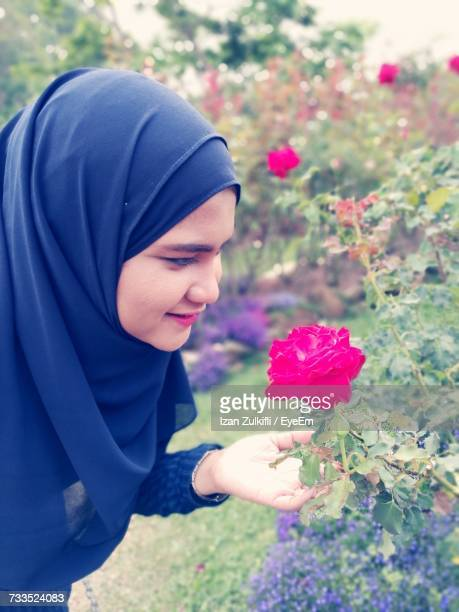 Close-Up Of Smiling Woman In Hijab Holding Pink Rose At Park