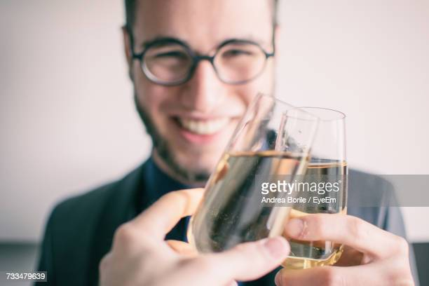 Close-Up Of Smiling Young Man Holding Drink