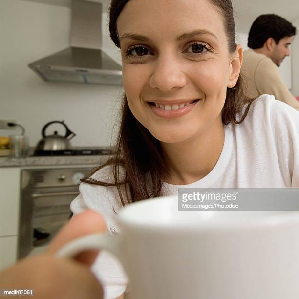 Close-up of smiling young woman holding coffee cup with man in background
