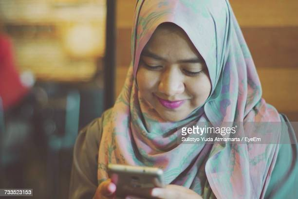 Close-Up Of Smiling Young Woman In Hijab Using Mobile Phone