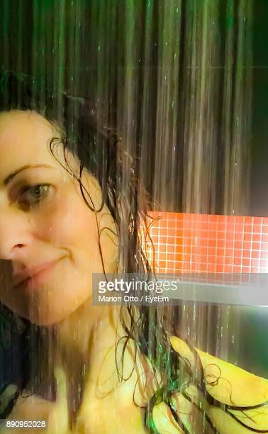 Close-Up Of Smiling Young Woman Taking Shower In Bathroom
