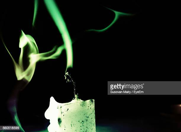 Close-Up Of Smoke Coming From Extinguished Candle Over Black Background