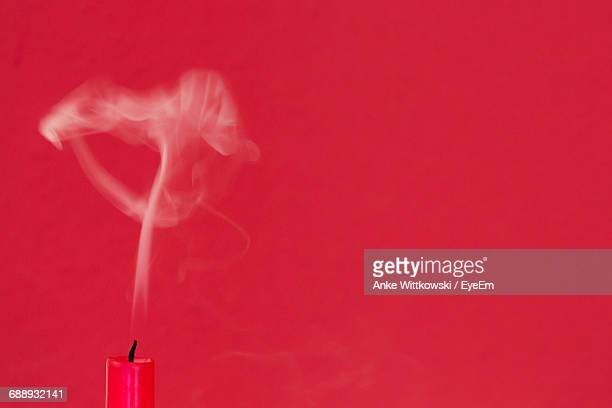 Close-Up Of Smoke Emitting Extinguished Candle Against Red Background